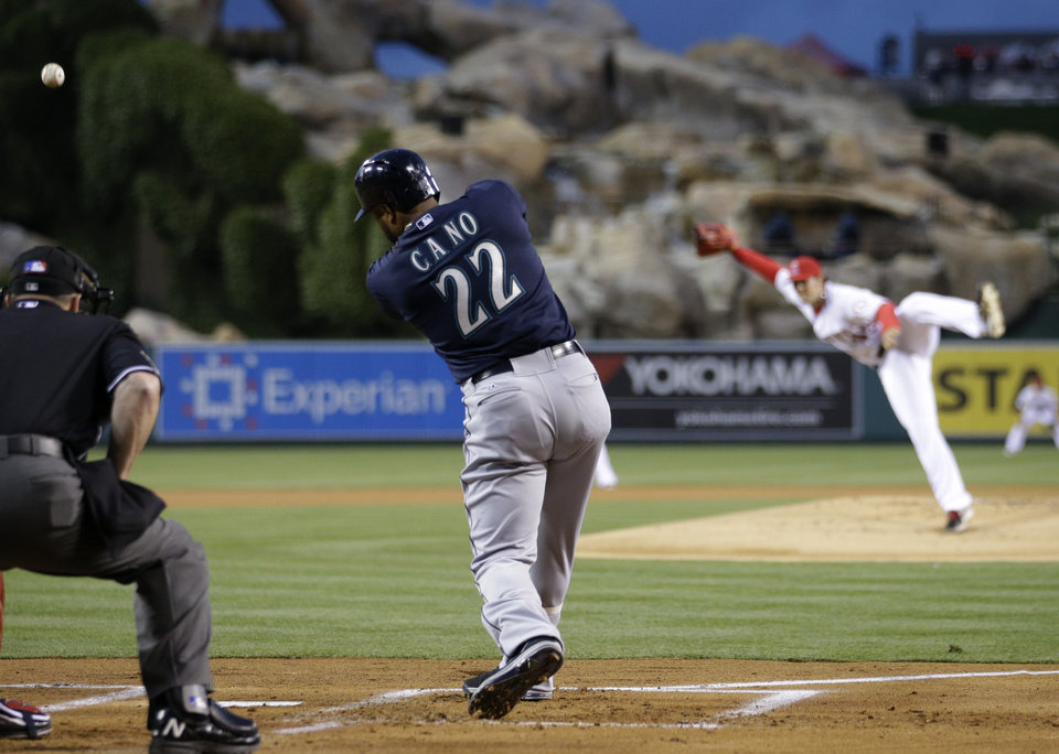 Photo - Seattle Mariners' Robinson Cano hits a fly ball off of Los Angeles Angels starting pitcher C.J. Wilson during the first inning of a baseball game on Tuesday, April 1, 2014, in Anaheim, Calif. (AP Photo/Jae C. Hong)