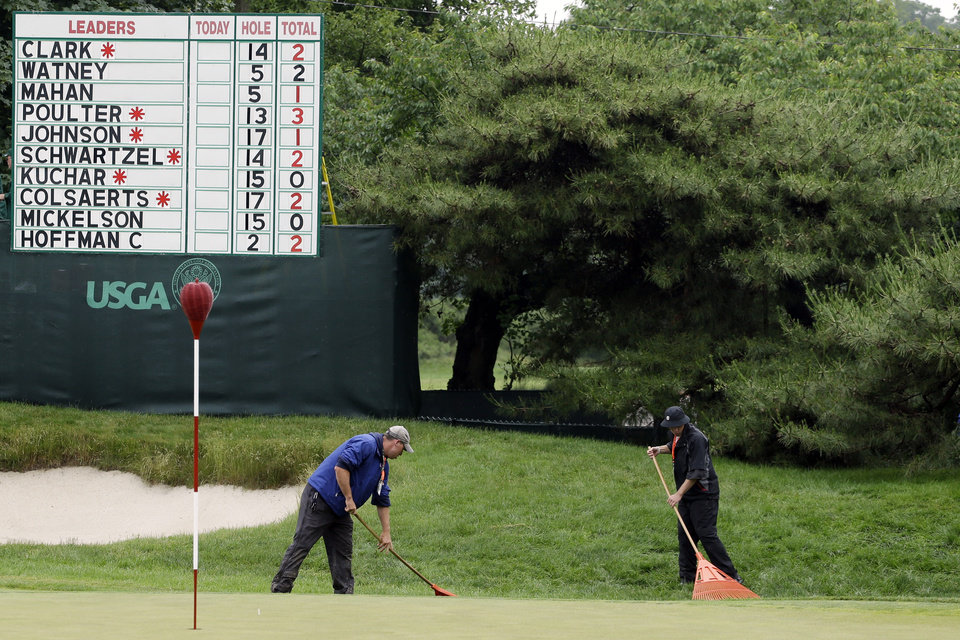 Photo - Course workers rake the first green after a weather delay in the first round of the U.S. Open golf tournament at Merion Golf Club, Thursday, June 13, 2013, in Ardmore, Pa. (AP Photo/Darron Cummings)