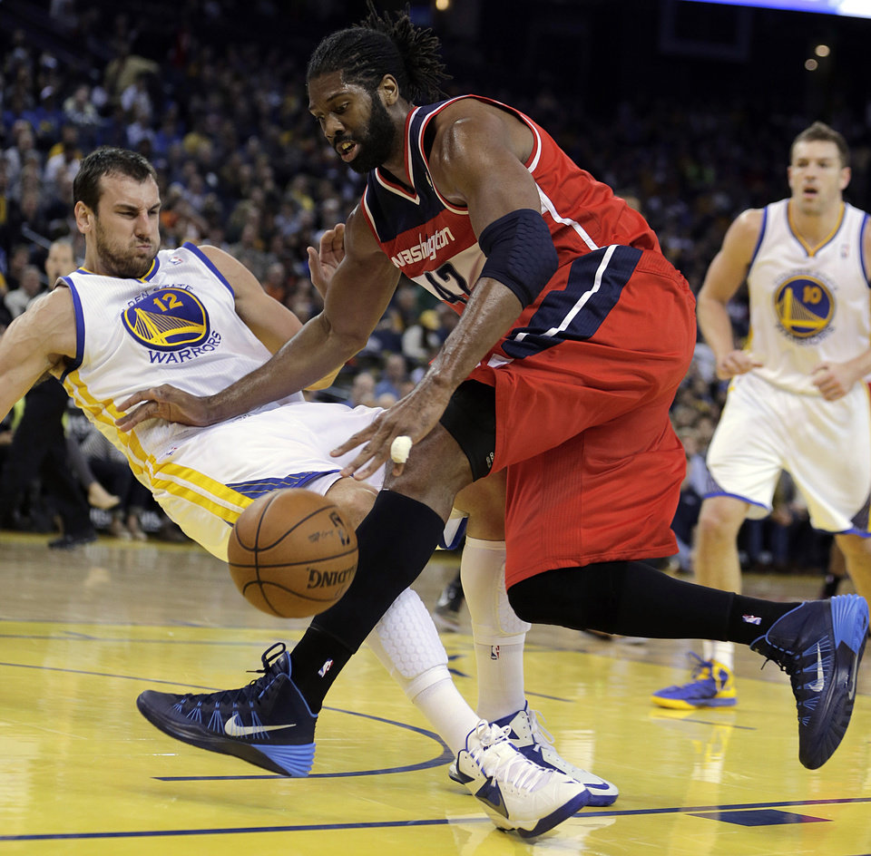 Photo - Washington Wizards' Nene Hilario, right, drives the ball into Golden State Warriors' Andrew Bogut (12) during the first half of an NBA basketball game, Tuesday, Jan. 28, 2014, in Oakland, Calif. (AP Photo/Ben Margot)
