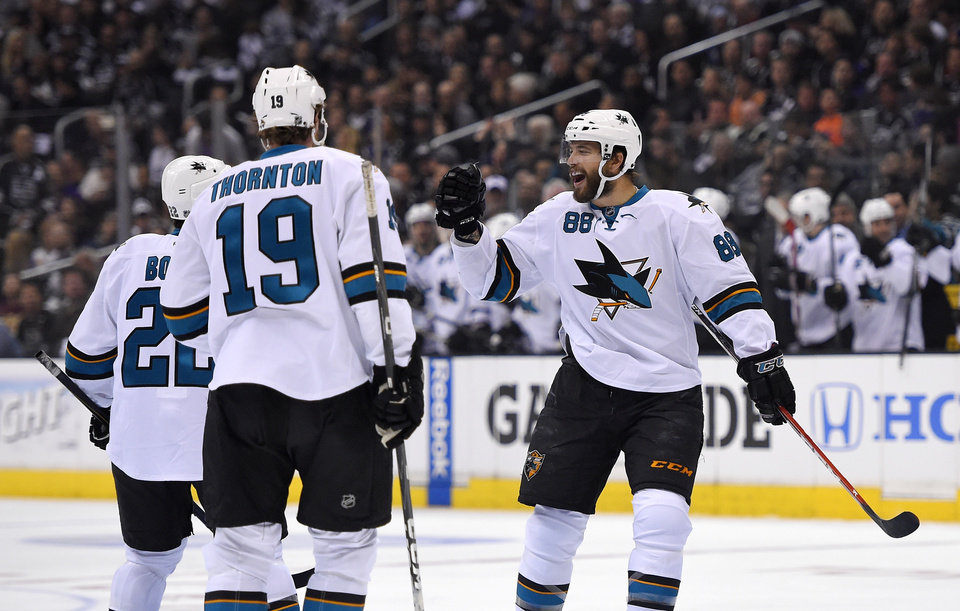 Photo - San Jose Sharks right wing Brent Burns, right, celebrates his goal with teammates defenseman Dan Boyle, left, and center Joe Thornton during the first period in Game 3 of an NHL hockey first-round playoff series , Tuesday, April 22, 2014, in Los Angeles. (AP Photo/Mark J. Terrill)