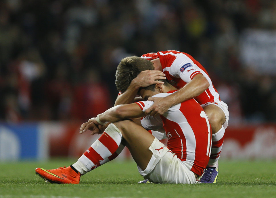 Photo - Arsenal's Mathieu Flamini, right, hugs teammate Alexis Sanchez at the end of their second leg Champions League qualifying soccer match between Arsenal and Besiktas at Emirates Stadium in London Wednesday, Aug. 27, 2014.(AP Photo/Kirsty Wigglesworth)