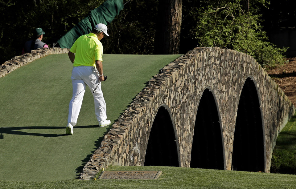 Photo - Lee Westwood, of England, walks over the Hogan Bridge on the 13th hole during the first round of the Masters golf tournament Thursday, April 10, 2014, in Augusta, Ga. (AP Photo/Charlie Riedel)