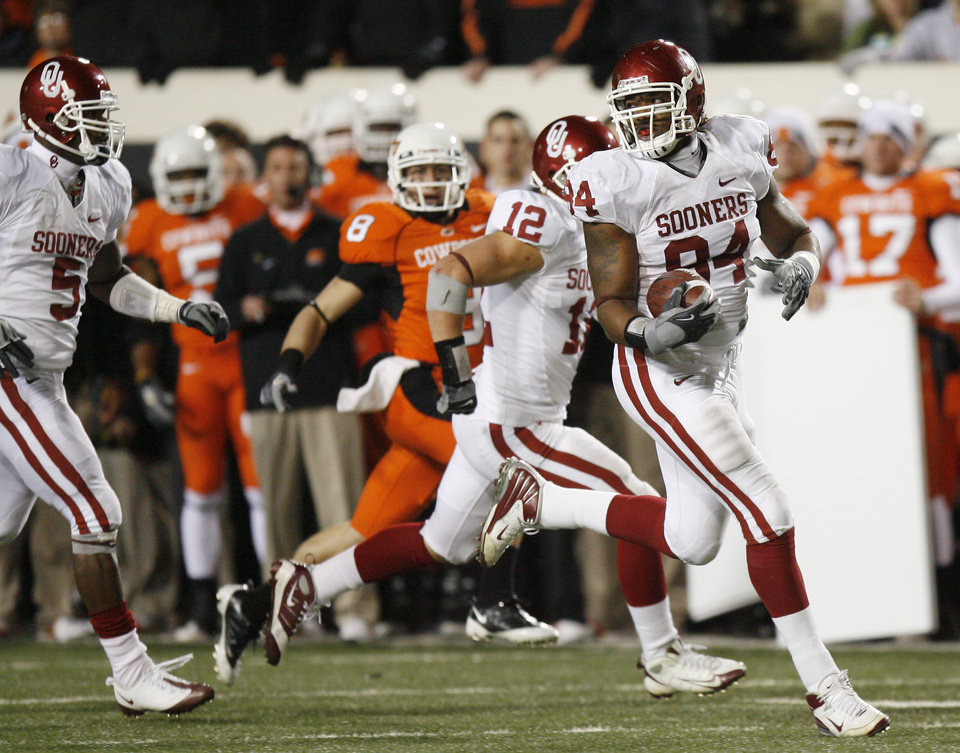 Frank Alexander picks up a Zac Robinson fumble on a two-point conversion try and runs it all the way during the second half of the college football game between the University of Oklahoma Sooners (OU) and Oklahoma State University Cowboys (OSU) at Boone Pickens Stadium on Saturday, Nov. 29, 2008, in Stillwater, Okla. STAFF PHOTO BY SARAH PHIPPS