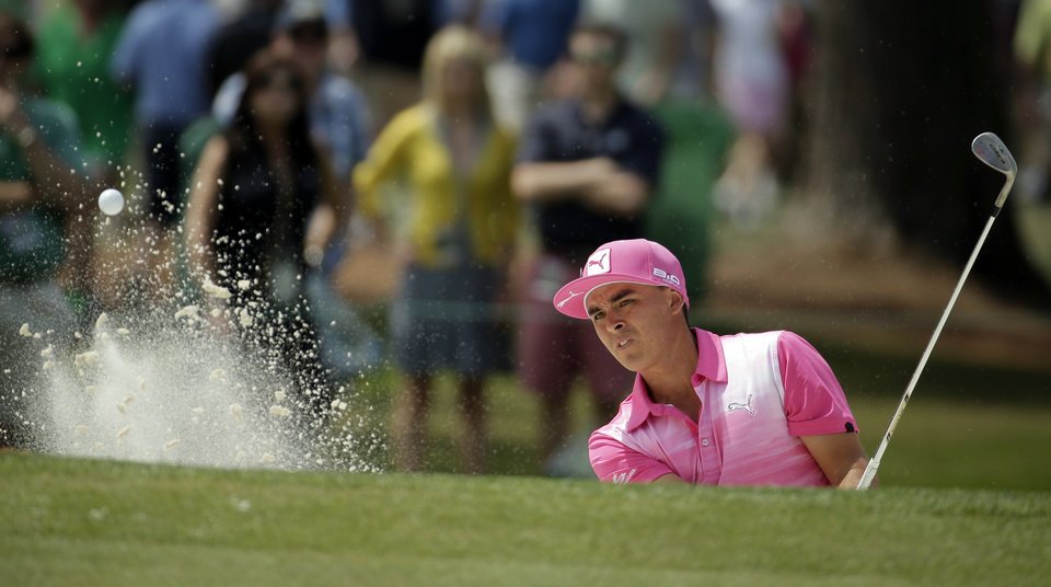 Photo - Rickie Fowler hits out a bunker on the seventh hole during the second round of the Masters golf tournament Friday, April 11, 2014, in Augusta, Ga. (AP Photo/Chris Carlson)