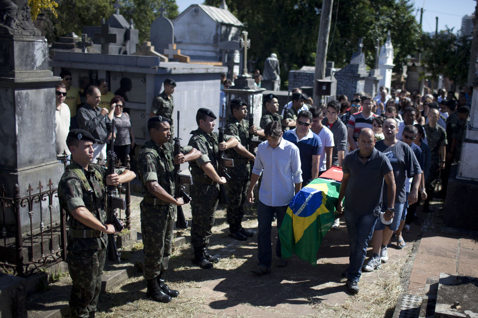 Photo - Soldiers stand, left, as relatives and friends carry the coffin during the burial of fire victim soldier Leonardo Machado, at a cemetery in Santa Maria city, Rio Grande do Sul state, Brazil, Monday, Jan. 28, 2013. A fast-moving fire roared through the crowded, windowless Kiss nightclub in southern Brazil early Sunday, within seconds filling the space with flames and smoke that killed more than 230 panicked partygoers who gasped for breath and fought in a stampede to escape. An early investigation into the tragedy revealed that security guards briefly prevented partygoers from leaving through the sole exit and the bodies later heaped inside that doorway slowed firefighters trying to get in (AP Photo/Felipe Dana)