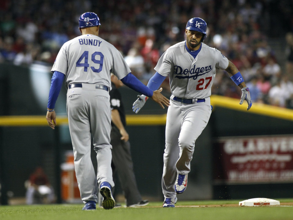 Photo - Los Angeles Dodgers' Matt Kemp (27) is congratulated by third base coach Lorenzo Bundy (49) as he rounds third after his solo home run against the Arizona Diamondbacks during the second inning of a baseball game on Sunday, April 13, 2014, in Phoenix. (AP Photo/Ralph Freso)