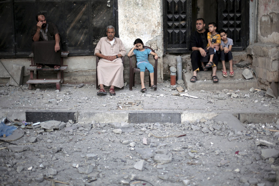 Photo - Neighbors of Palestinian Hamas leader, Mahmoud Zahar, sit outside their homes following an early morning Israeli missile strike that destroyed Zahar's house in Gaza City, Wednesday, July 16, 2014. Israel on Wednesday intensified air attacks on Hamas targets in the Gaza Strip following a failed Egyptian cease-fire effort, targeting the homes of four senior leaders of the Islamic militant movement and ordering tens of thousands of residents to evacuate border areas. (AP Photo/Khalil Hamra)