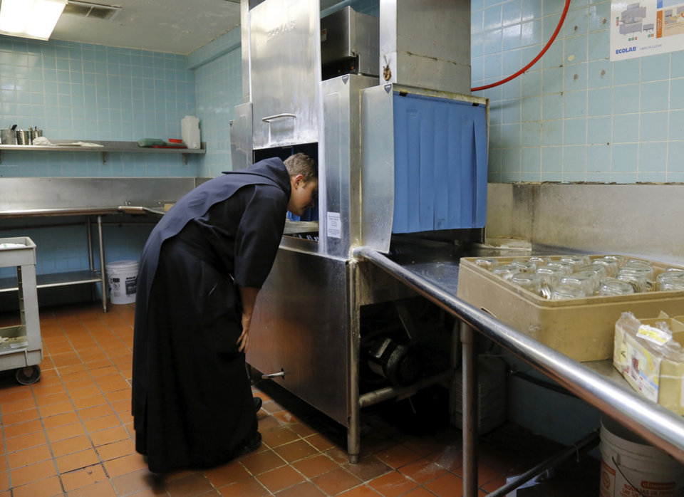 Photo -  The Rev. Simeon Spitz sticks his head inside a dishwasher to look for one of the lids to his jars before he prepares blackberry jam at St. Gregory's Abbey. Photo by Jim Beckel, The Oklahoman   Jim Beckel