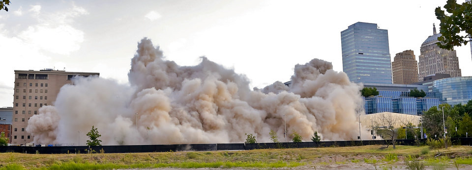 Photo - A cloud of dust fills the air as the Hotel Black and the adjoining parking garage in downtown Oklahoma City are taken down during an implosion by Midwest Wrecking Company on Sunday, Sept. 13, 2015, in Oklahoma City, Okla.  Photo by Chris Landsberger, The Oklahoman