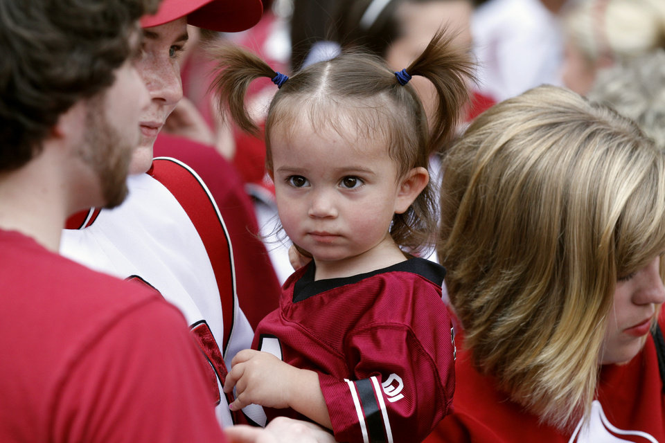 Photo - Claire Hasan, one-year-old, is carried through the OU Band outside the Oklahoma Memorial Union by her aunt, flag corp member Laura Morris before the college football game between the University of Oklahoma Sooners (OU) and the Tulsa University Hurricanes (TU) at the Gaylord Family-Memorial Stadium on Saturday, Sept. 3, 2011, in Norman, Okla. 
