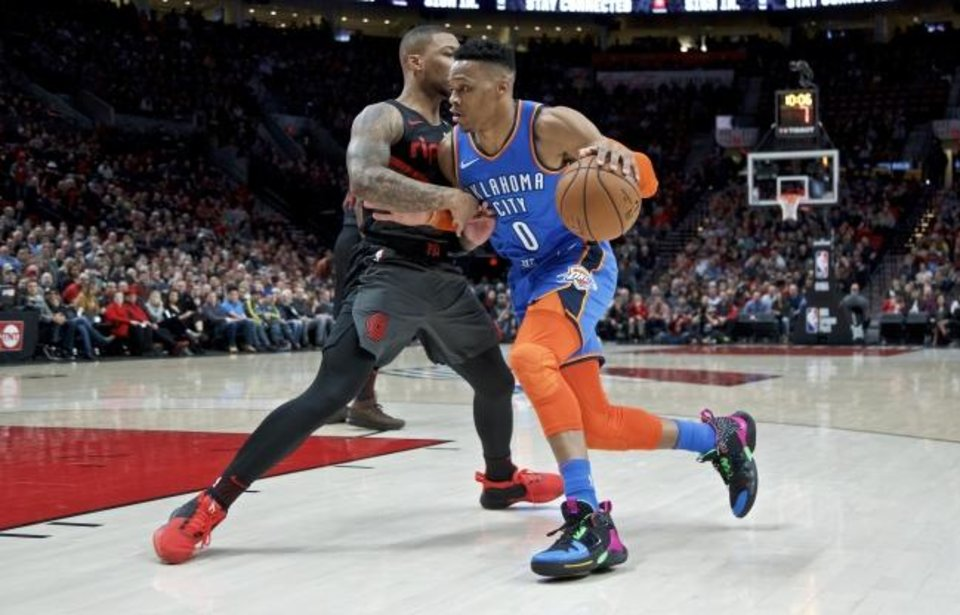Photo -  Oklahoma City Thunder guard Russell Westbrook, right, drives Portland Trail Blazers guard Damian Lillard during the first half of Thursday night's NBA game in Portland, Ore. [AP Photo/Craig Mitchelldyer]
