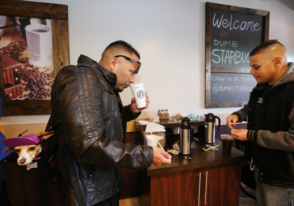 Photo - Anthony Solis, left, and Tony Gonzalez prepare their coffee at the Dumb Starbucks coffee  shop in Los Angeles Monday, Feb. 10, 2014. The store resembles a Starbucks with a green awning and mermaid logo, but with the word