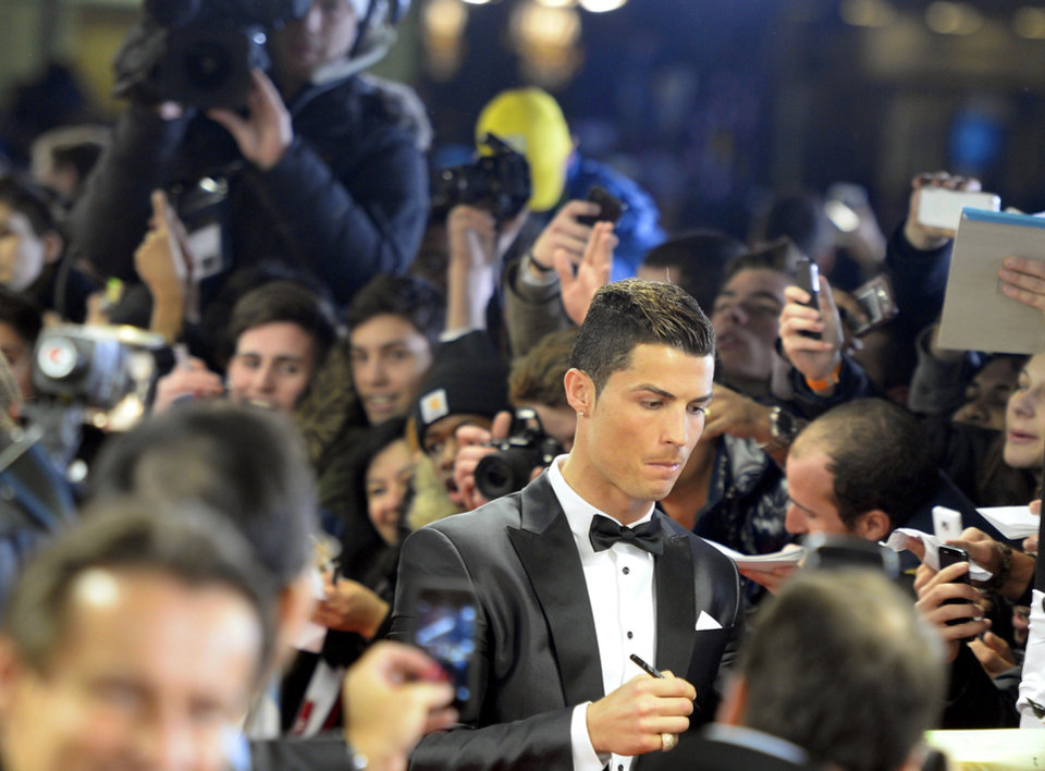 Photo - Soccer player Cristiano Ronaldo of Portugal signs autographs on the red carpet prior to the FIFA Ballon d'Or 2013 gala held at the Kongresshaus in Zurich, Switzerland, Monday, Jan. 13, 2014. (AP Photo/Keystone,Walter Bieri)