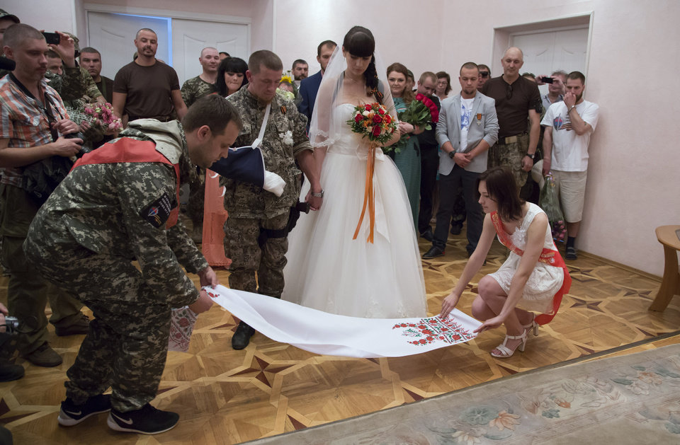 Photo - Pavel Gubarev, left, a leader of the self-proclaimed Donetsk People's Republic, attends the wedding ceremony of platoon commander Arsen Pavlov, also known as Motorola, and Elena Kolenkina in the city of Donetsk, eastern Ukraine Friday July 11, 2014. (AP Photo/Dmitry Lovetsky)