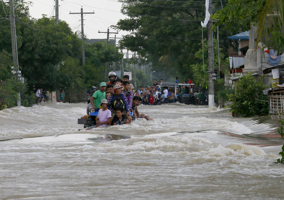 Photo - Commuters ride a farm tractor as it maneuvers through strong floodwaters along a highway in La Paz township, Tarlac province in northern Philippines Tuesday, Oct. 20, 2015. Two days after Typhoon Koppu battered northern Philippines residents began cleaning up their muddied homes. (AP Photo/Bullit Marquez)