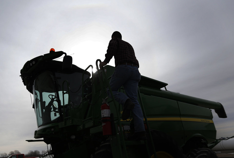 Photo - Nick Guetterman climbs into a combine on his farm near Bucyrus, Kan., Wednesday, Feb. 19, 2014.  Farmers from across the nation gathered in Washington this month for their annual trek to seek action on the most important matters in American agriculture.  But this time, a new issue emerged: growing unease about how the largest seed companies are gathering vast amount of data from sensors on tractors, combines and other farm equipment. The sensors measure soil conditions, seeding rates, crop yields and many other variables.  (AP Photo/Orlin Wagner)