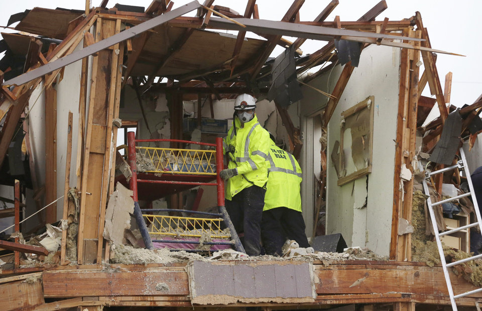 Photo - A firefighter handles a children's bunk bed during a search and rescue of an apartment destroyed by an explosion at a fertilizer plant in West, Texas, Thursday, April 18, 2013.  A massive explosion at the West Fertilizer Co. killed as many as 15 people and injured more than 160, officials said overnight.  (AP Photo/LM Otero)