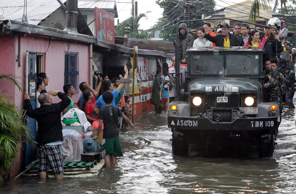 This Aug. 8, 2012 photo released by the Malacanang Photo Bureau shows Philippine President Benigno Aquino III, center, as he waves to residents staying outside their homes along flooded areas during his visit in Muntinlupa, south of Manila, Philppines. Widespread flooding battered millions of homes and paralyzed the Philippine capital as rescue efforts focused on a large number of distressed residents who are still marooned on their roof tops. (AP Photo/Malacanang Photo Bureau, HO) NO SALES ORG XMIT: XAF813