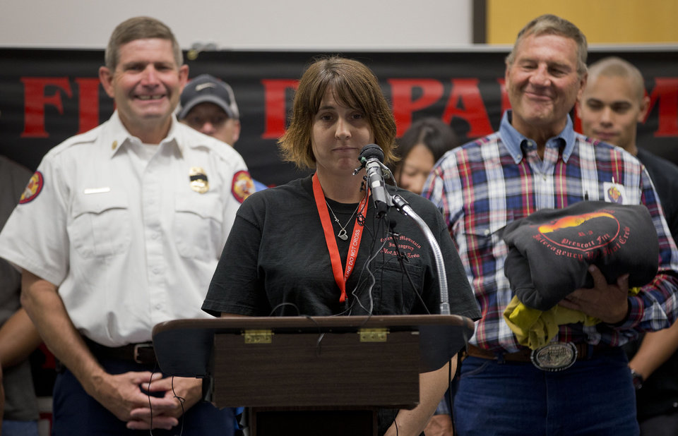 Flanked by Prescott Fire Chief Darrel Willis, left, and retired chief Dwayne Steinbrink, right, Amanda Marsh, center, widow of Granite Mountain Hotshot Crew superintendent Eric Marsh, speaks during a news conference, Thursday, July 4, 2013 in Prescott, Ariz. Eric Marsh, who founded the Granite Mountain Hotshots, was one of the 19 Hotshot firefighters who were killed by an out-of-control blaze on Sunday near Yarnell, Ariz.  (AP Photo/Julie Jacobson)