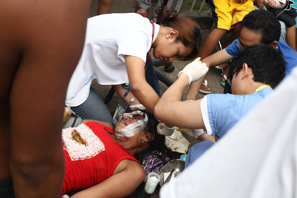 Photo - Doctors treat a woman outside a damaged Vicente Sotto Hospital in Cebu, central Philippines on Tuesday Oct. 15, 2013. A 7.2-magnitude earthquake collapsed buildings, cracked roads and toppled the bell tower of the Philippines' oldest church Tuesday morning, killing at least 20 people across the central region. (AP Photo/Chester Baldicantos)