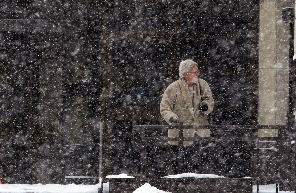 Photo - Snow continues to fall in downtown St. Joseph, Mo., as people exit the Missouri State building Tuesday, Feb. 4, 2014. (AP Photo/The St. Joseph News-Press, Todd Weddle)