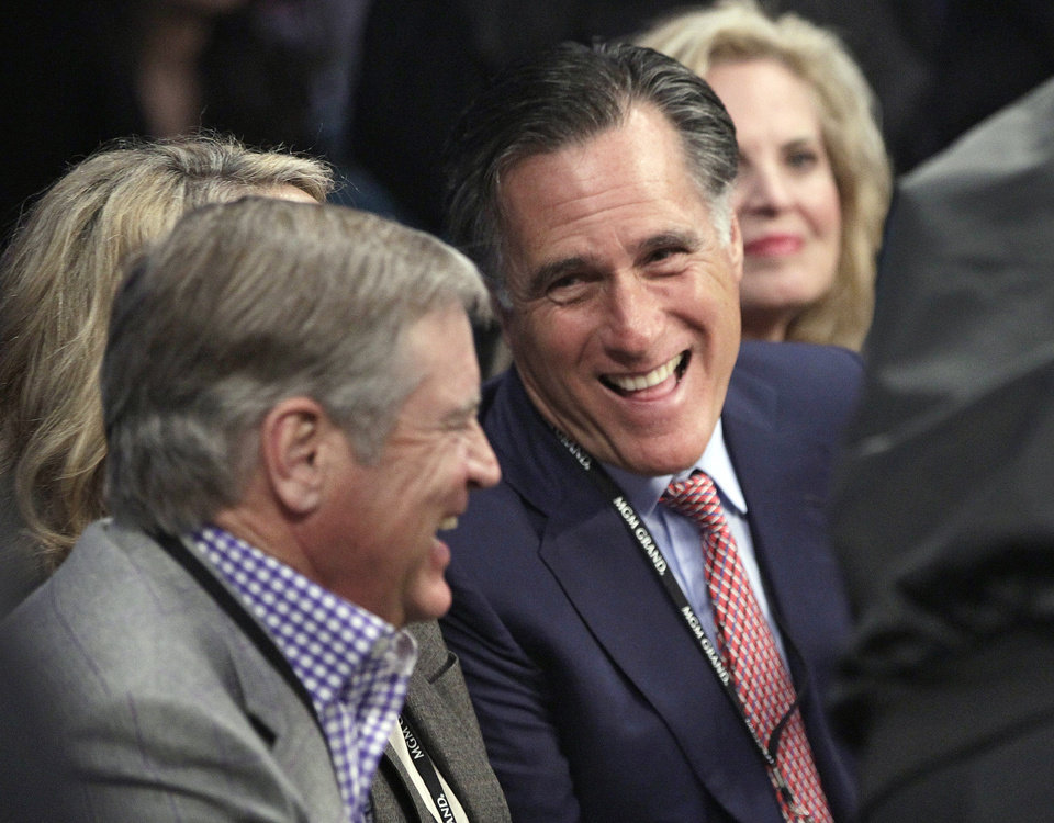 FILE - In this Dec. 8, 2012, file photo, former Republican presidential candidate Mitt Romney, center, joined by wife Ann, right, talks with an unidentified spectator at ringside prior to a welterweight fight between Juan Manuel Marquez and Manny Pacquiao title fight in Las Vegas. Romney has emerged from nearly four months in seclusion for an interview with Fox News. He's also scheduled to deliver his first postelection speech this month at Washington's Conservative Political Action Conference. (AP Photo/Julie Jacobson, File)