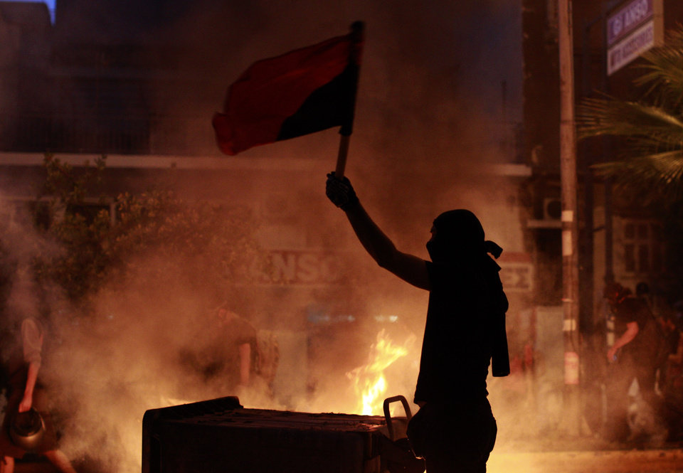 Photo - A protester waves a flag in front of a burning barricade during a protest, after the stabbing of a 34 year old man in the suburb of Keratsini near Athens , Wednesday, Sept. 18,  2013.  Violent clashes broke out Wednesday in several Greek cities after a member of the country's far-right Golden Dawn party was arrested in the fatal stabbing of a 34-year-old musician described as an anti-fascist activist. The stabbing drew condemnation from across Greece's political spectrum and from abroad. While the extremist Golden Dawn has been blamed for numerous violent attacks in the past, the overnight stabbing is the most serious violence directly attributed to a member so far. (AP Photo/Kostas Tsironis)