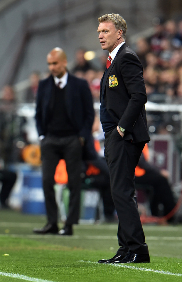 Photo - Manchester United's manager David Moyes, right, and Bayern head coach Pep Guardiola of Spain, left, attend the Champions League quarterfinal second leg soccer match between Bayern Munich and Manchester United in the Allianz Arena in Munich, Germany, Wednesday, April 9, 2014. (AP Photo/Kerstin Joensson)