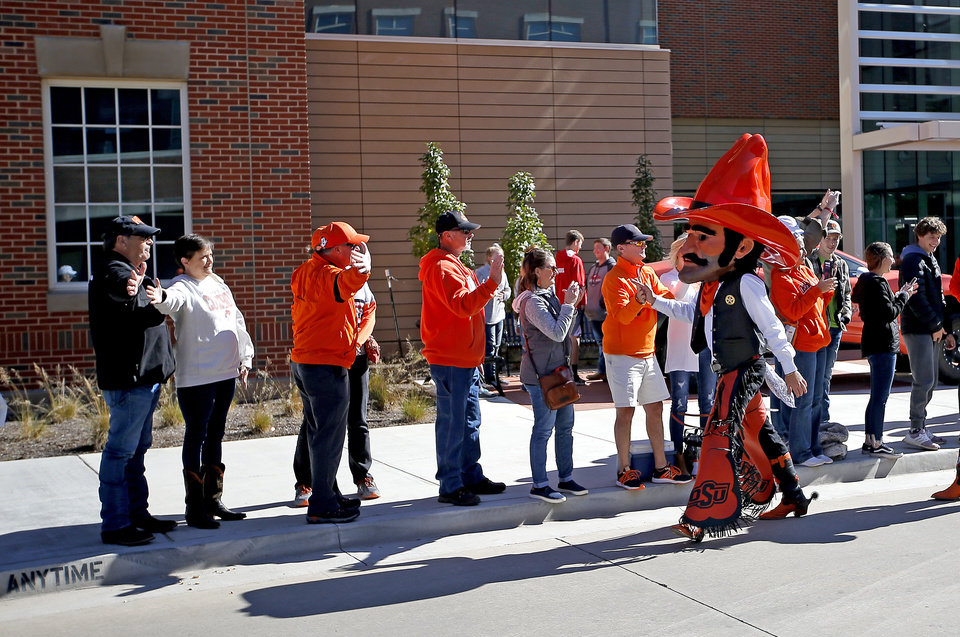 Photo - Pistol Pete high fives fans at the walk before the college football game between the Oklahoma State University Cowboys and the TCU Horned Frogs at Boone Pickens Stadium in Stillwater, Okla.,  Saturday, Nov. 2, 2019. [Sarah Phipps/The Oklahoman]