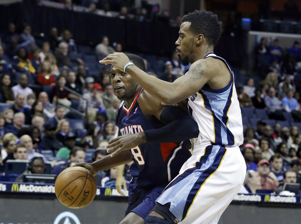 Photo - Memphis Grizzlies' Mike Conley, right, defends against Atlanta Hawks' Shelvin Mack (8) in the first half of an NBA basketball game in Memphis, Tenn., Sunday, Jan. 12, 2014. (AP Photo/Danny Johnston)