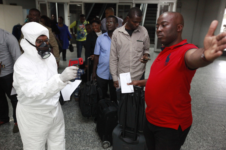 Photo - FILE - In this Wednesday, Aug. 6, 2014 file photo, a Nigerian port health official uses a thermometer on a passengers at the arrivals hall of Murtala Muhammed International Airport in Lagos, Nigeria. Two new cases of Ebola have emerged in Nigeria and, in an alarming development, they are outside the group of caregivers who treated an airline passenger who arrived with Ebola and died, Health Minister Onyebuchi Chukwu said Friday, Aug. 22, 2014. (AP Photo/Sunday Alamba, File)