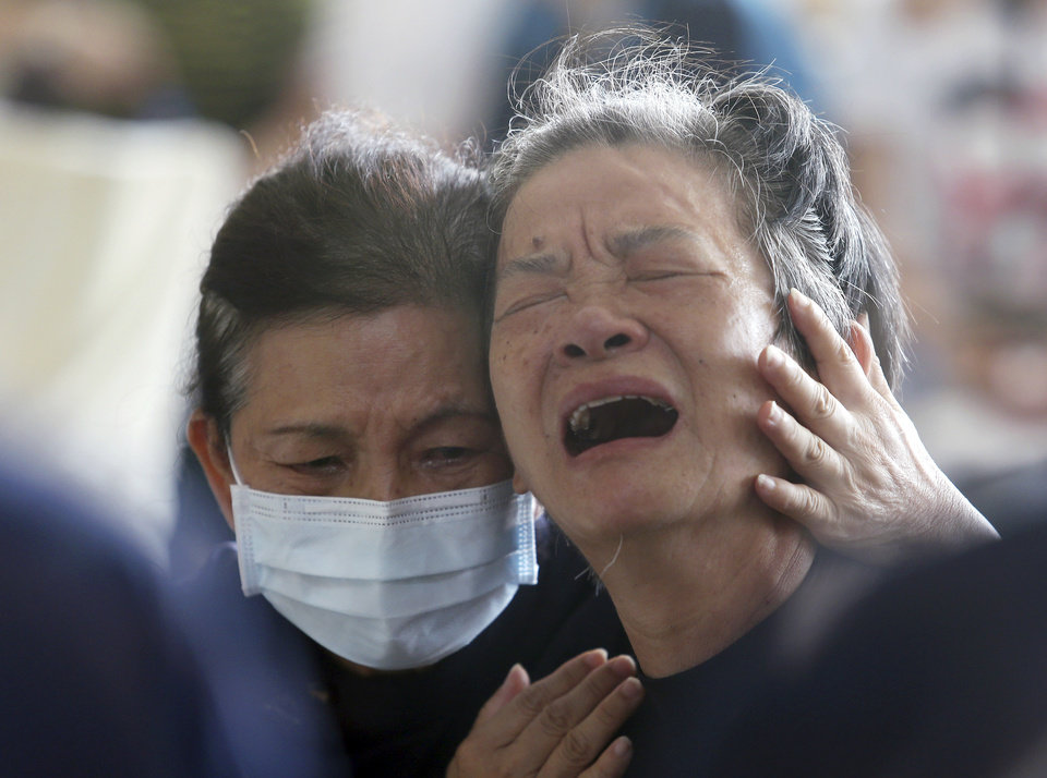 Photo - A relative, right, of a victim in the multiple explosions from an underground gas leak is consoled at a funeral parlor in Kaohsiung, Taiwan, Friday, Aug. 1, 2014. A series of explosions about midnight Thursday and early Friday ripped through Taiwan's second-largest city, killing scores of people, Taiwan's National Fire Agency said Friday. (AP Photo) TAIWAN OUT