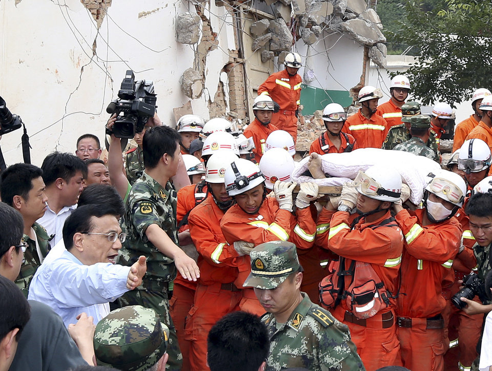 Photo - Chinese Premier Li Keqiang helps make way for the injured at the earthquake zone in the town of Longtoushan in Ludian County in southwest China's Yunnan Province Monday, Aug. 4, 2014. Li walked into Longtoushan township of Ludian County Monday to examined the situation of the earthquake and instructed the quake relief work. (AP Photop/Xinhua, Yao Dawei) NO SALES