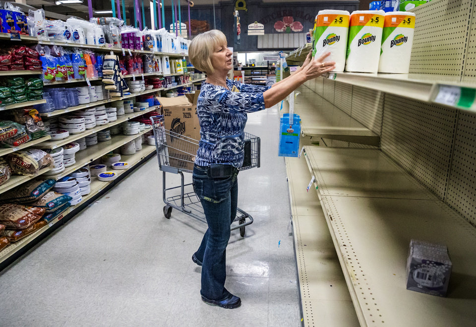 Photo - Assistant manager Betty Black stocks her last box of paper towels at the Homeland grocery store located at 2400 S. Cornwell in Yukon, Okla. on Thursday, March 19, 2020. Homeland has dedicated the first hour of store operations to senior customers and those who have medical conditions that put them at risk from COVID-19.  [Chris Landsberger/The Oklahoman]