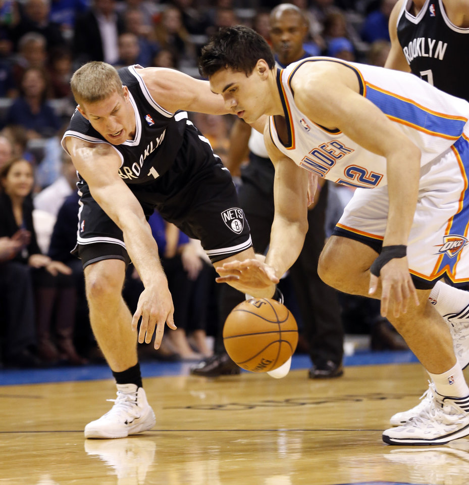Thunder's Steven Adams (12) and Brooklyn's Mason Plumlee (1) fight for the ball in an NBA basketball game between the Oklahoma City Thunder and the Brooklyn Nets at the Chesapeake Energy Arena in Oklahoma City, on Thursday, Jan. 2, 2014.  Photo by Steve Sisney, The Oklahoman