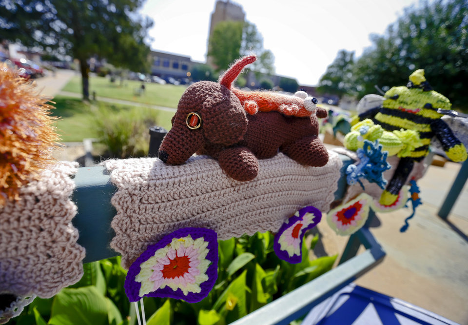 Photo - Knitted art is displayed in the Enid town square as part of the Yarnover Enid community art event on Friday, Sept. 6, 2013 in Enid, Okla. The public art project was established to bring the town together to display 'art graffiti' created from items made and donated by the community.  Photo by Chris Landsberger, The Oklahoman