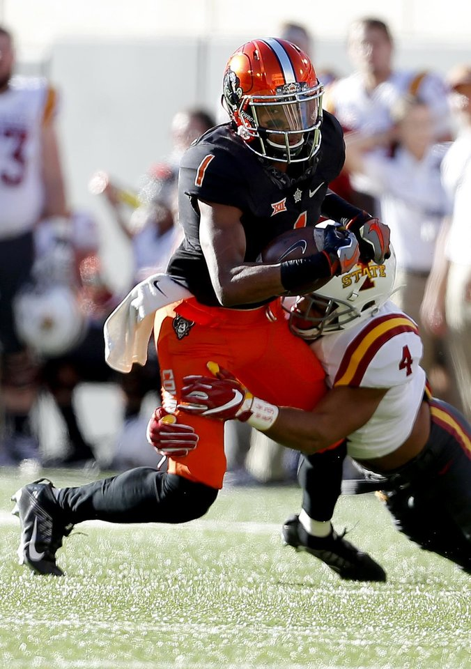 Photo - Oklahoma State's Jalen McCleskey (1) is brought down by Iowa State's Evrett Edwards (4) in the third quarter during a college football game between the Oklahoma State University Cowboys (OSU) and the Iowa State University at Boone Pickens Stadium in Stillwater, Okla., Saturday, Oct. 8, 2016. Photo by Sarah Phipps, The Oklahoman