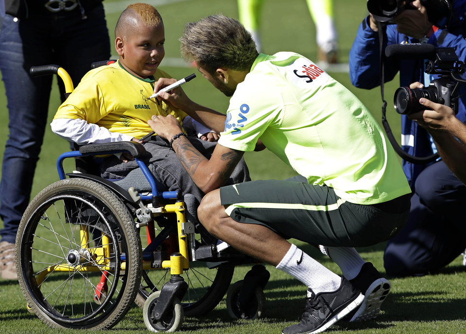 Photo - Brazil's Neymar autographs a fan's jersey prior to a training session in Teresopolis, Brazil, Wednesday, June 25, 2014. About fifty children that were victims of floods and landslides in Rio de Janeiro state in 2011 watched the training. Brazil will face Chile on June 28 in the round of 16 of the 2014 soccer World Cup. (AP Photo/Andre Penner)
