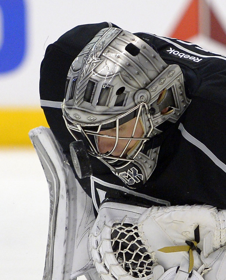 Photo - Los Angeles Kings goalie Jonathan Quick stops a shot with his mask during the first period of an NHL hockey game against the Carolina Hurricanes, Saturday, March 1, 2014, in Los Angeles. (AP Photo/Mark J. Terrill)