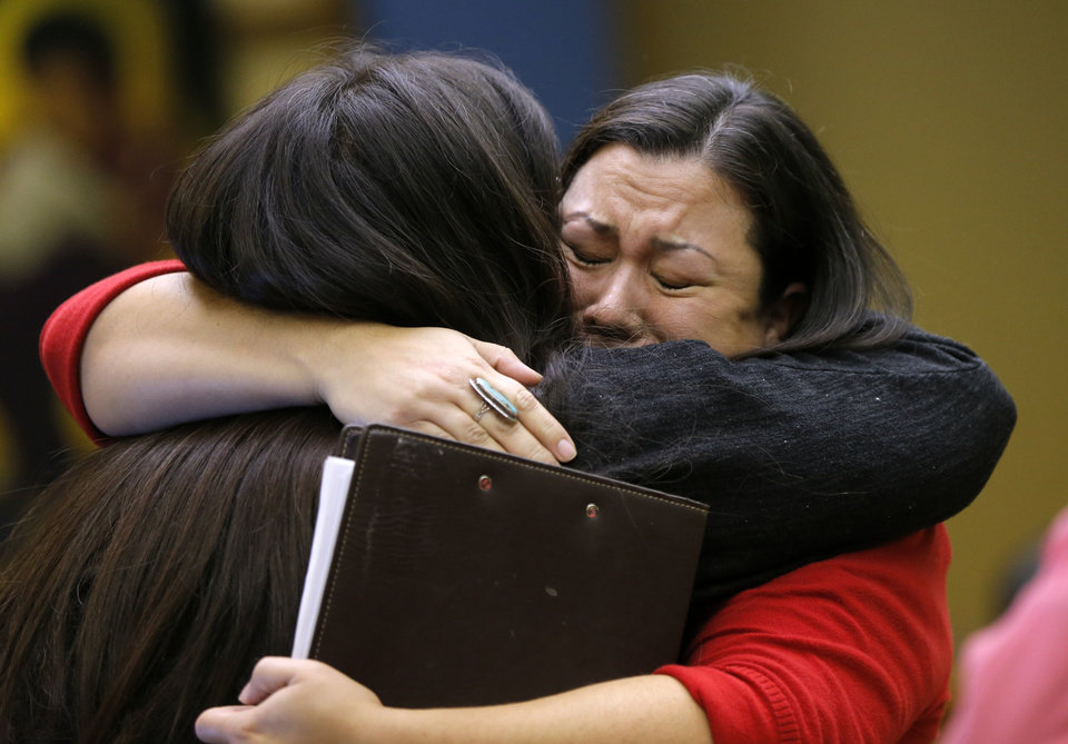 Photo - Sarah Adams-Cornell, Choctaw Nation, right, and Alecia Onzahwah, Absentee Shawnee, hug Monday after the school board voted unanimously to dismiss the Redskins as the mascot for Capitol Hill High School.  Photo by  Nate Billings,  The Oklahoman  NATE BILLINGS -  NATE BILLINGS