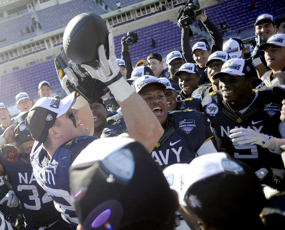Navy players celebrate with the trophy after their 24-6 win over Middle Tennessee in the Armed Forces Bowl NCAA college football game, Monday, Dec. 30, 2013, in Fort Worth, Texas. (AP Photo/Matt Strasen)