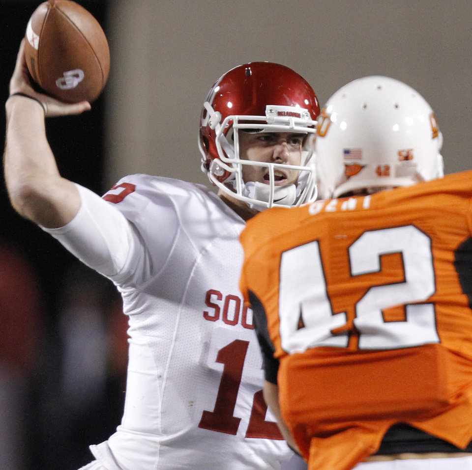 Photo - Oklahoma's Landry Jones (12) throws a pass in front of Oklahoma State's Justin Gent (42) during the Bedlam college football game between the University of Oklahoma Sooners (OU) and the Oklahoma State University Cowboys (OSU) at Boone Pickens Stadium in Stillwater, Okla., Saturday, Nov. 27, 2010. Photo by Chris Landsberger, The Oklahoman