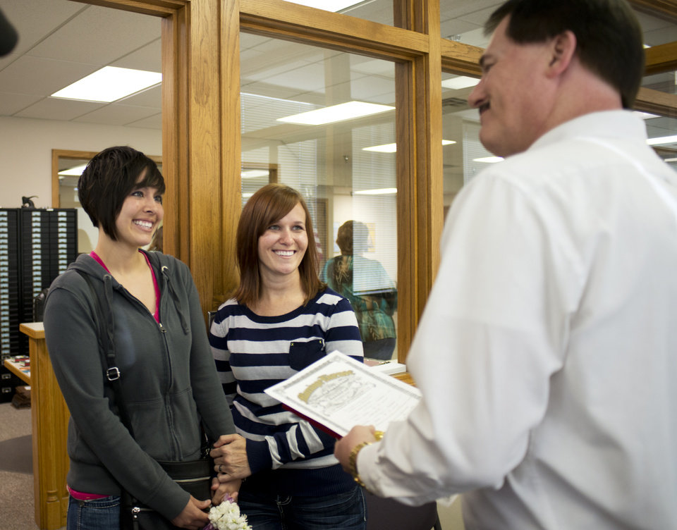 Photo - Beth Moore, left, and her partner Abby Hill, center, exchange vows in a marriage ceremony performed by Jeremy Hernandez, right, at the Washington County Courthouse in Fayetteville, Ark., Friday May 16, 2014.  The Washington County clerk has resumed issuing marriage licenses to same-sex couples, a day after a circuit judge in Pulaski County ruled that all state laws barring gay marriage are unconstitutional. (AP Photo/Sarah Bentham)