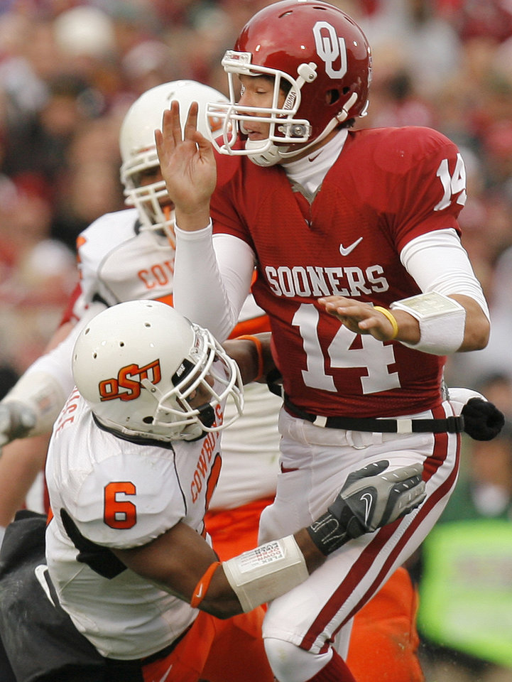 Photo - BEDLAM: Oklahoma's Sam Bradford (14) takes a hit by Oklahoma State's Ricky Price (6) during the first half of the college football game between the University of Oklahoma Sooners (OU) and the Oklahoma State University Cowboys (OSU) at the Gaylord Family -- Oklahoma Memorial Stadium on Saturday, Nov. 24, 2007, in Norman, Okla.   Photo By NATE BILLINGS, The Oklahoman ORG XMIT: KOD