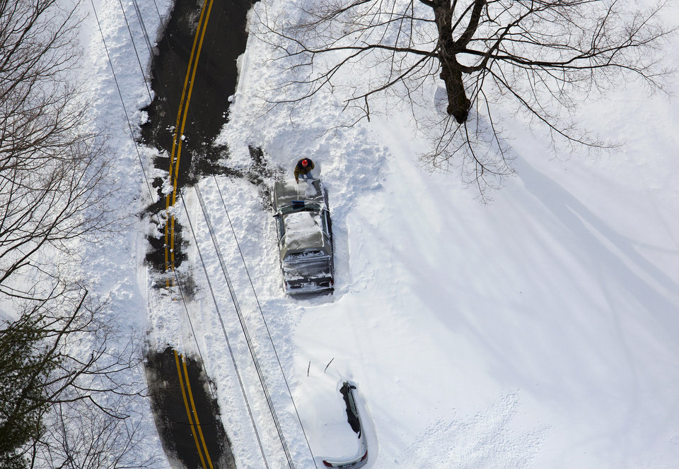Photo - A person digs out a can near Hamden, Conn., Sunday, Feb. 10, 2013, in the aftermath of a storm that hit Connecticut and much of the New England states. (AP Photo/Craig Ruttle)