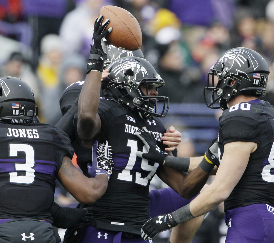 Photo -   Northwestern wide receiver Cameron Dickerson (19) celebrates with teammates after recovering a fumble by Illinois defensive back Justin Green (26) during the first half of an NCAA college football game in Evanston, Ill., Saturday, Nov. 24, 2012. (AP Photo/Nam Y. Huh)