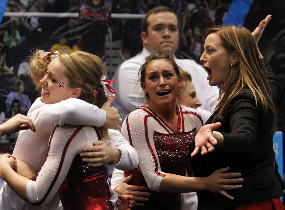 Photo - Oklahoma coach KJ Kindler, right, celebrates with team after their vault routine during the NCAA women's gymnastics championships on Saturday, April 19, 2014, in Birmingham, Ala. (AP Photo/Butch Dill)