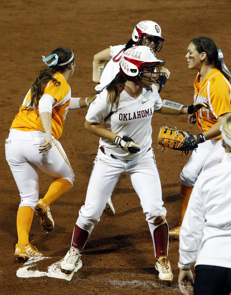 Photo - Oklahoma has too many runners at third as Erin Miller holds up and Oklahoma's Destinee Martinez tries to advance when a throw bounces off Miller as the University of Oklahoma Sooner (OU) softball team plays Tennessee in the first game of the NCAA super regional at Marita Hynes Field on May 23, 2014 in Norman, Okla. Photo by Steve Sisney, The Oklahoman