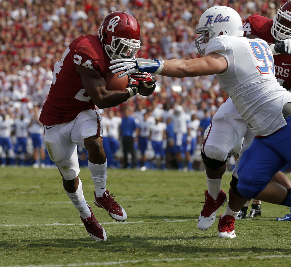 Photo - Oklahoma's Brennan Clay (24) runs past Tulsa's Hayden Carman (95) for a touchdown during a college football game between the University of Oklahoma Sooners (OU) and the Tulsa Golden Hurricane at Gaylord Family-Oklahoma Memorial Stadium in Norman, Okla., on Saturday, Sept. 14, 2013. Photo by Bryan Terry, The Oklahoman