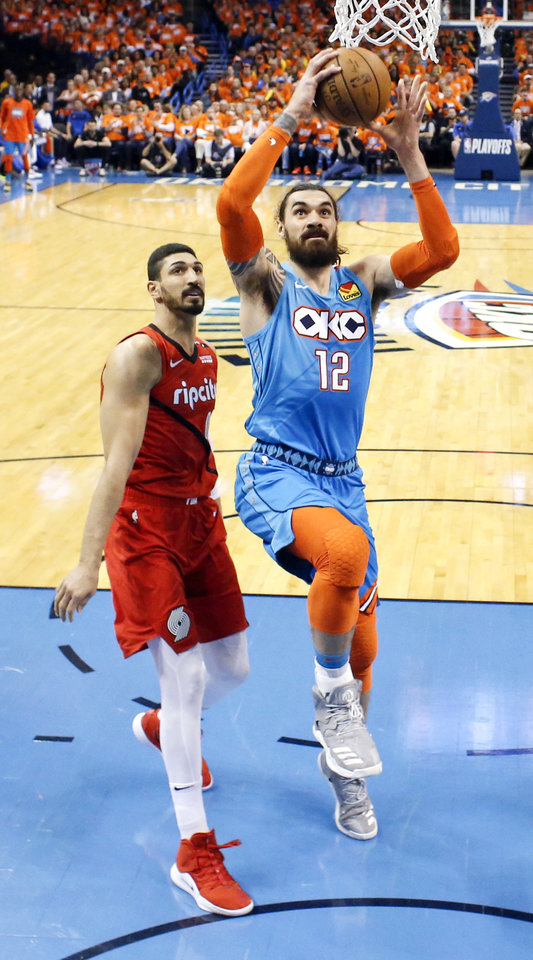 Photo - Oklahoma City's Steven Adams (12) takes the ball to the basket past Portland's Enes Kanter (00) in the first half during Game 3 in the first round of the NBA playoffs between the Portland Trail Blazers and the Oklahoma City Thunder at Chesapeake Energy Arena in Oklahoma City, Friday, April 19, 2019. Photo by Nate Billings, The Oklahoman